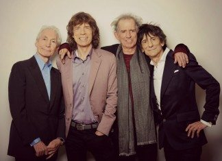 Los Rolling Stones posan sonrientes ante un fondo blanco que destaca sus arrugas de viejas glorias del rock and roll