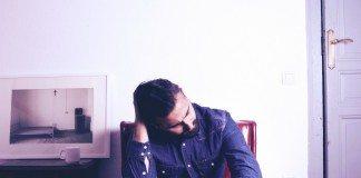 Daniel Van Lion sentado junto a una foto en una habitación. Fotografía de lázaroylorenzo
