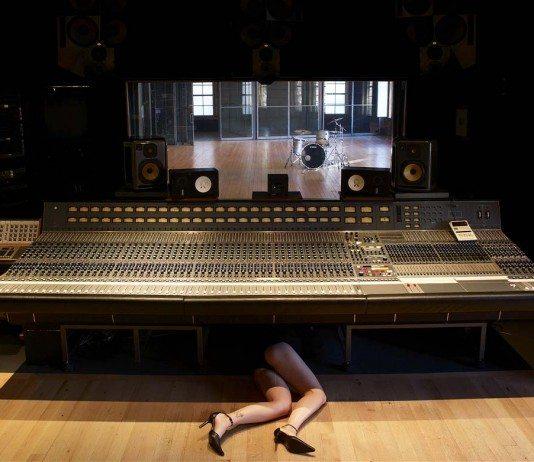 Mesa de mezclas en estudio y una chica en el suelo