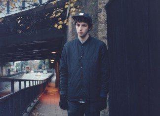 Jamie xx con un abrigo bajo un puente.