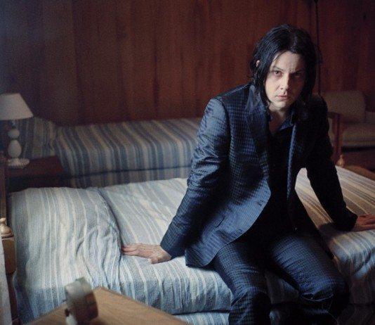 Jack White sentado en una cama