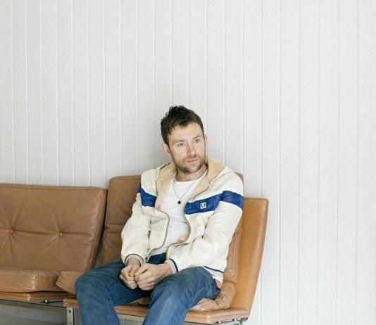 Damon Albarn en sillón marrón