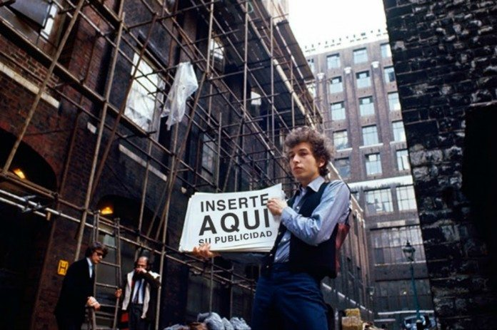 Bob Dylan en la calle muestra una pancarta publicitaria.