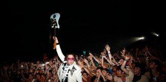 Win Butler entre el público y una guitarra en alto
