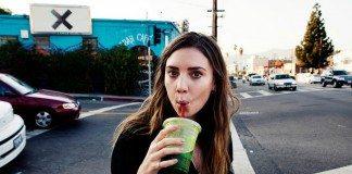Lykke Li bebe un zumo en la calle.