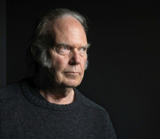 Neil Young con un jersey gris en un fondo oscuro