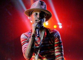 Pharrell WIlliams con sombrero y camiseta a rayas cantando en directo.