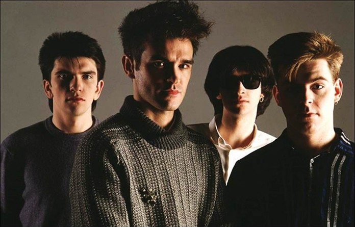 The Smiths de oscuro con un fondo gris