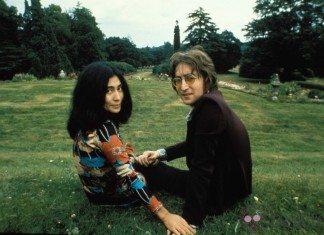 Yoko Ono y John Lennon sentados en un parque