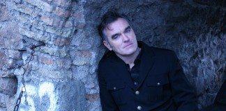 Morrissey apoyado en una pared de piedra con el número 52 pintado