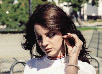 Lana del Rey con una camiseta blanca y un verja al fondo