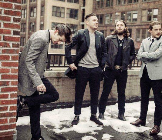 Alex Turner fumando junto al resto de Arctic Monkeys sobre un edificio.