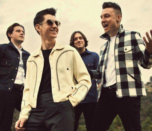 Arctic Monkeys sonríen junto a la ladera del campo.