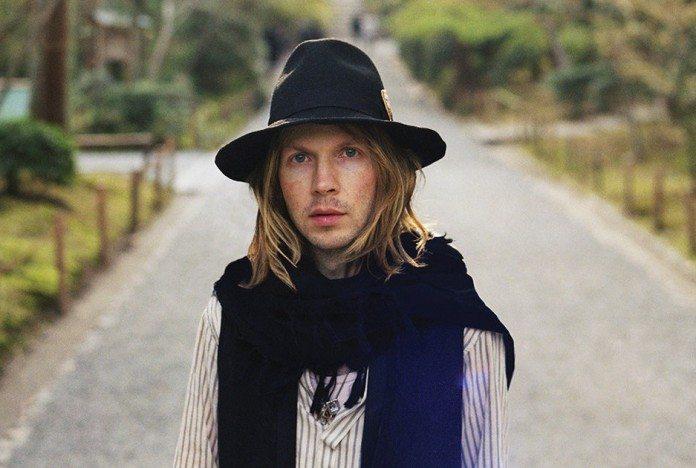 Beck con sombrero y pelo largo