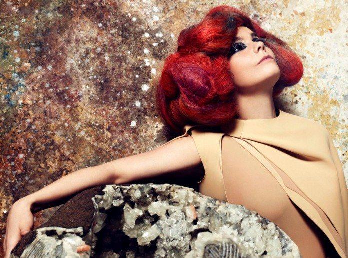 Brjörk con el pelo rojo sujetando una roca