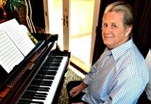 Brian Wilson en un taburete en el estudio junto al piano.