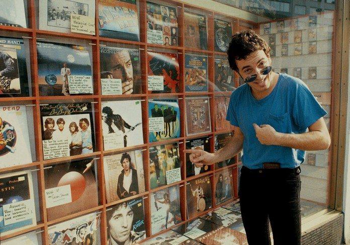 Bruce Springsteen señala sus álbumes en el escaparate de una tienda de discos.