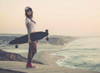 Chica con monopatín en el muelle de una playa.