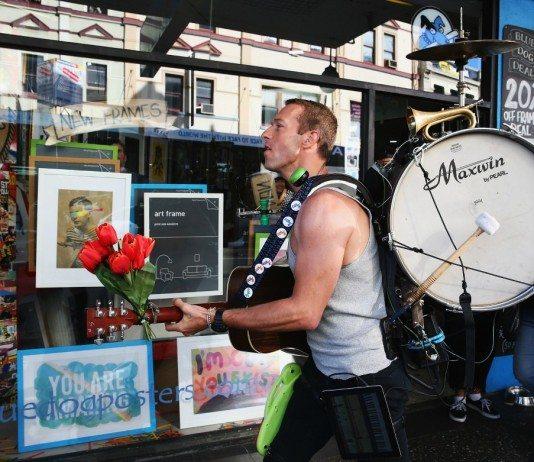 Chris Martin de Coldplay con un tambor a la espada frente a una tienda de posters.