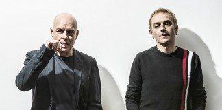 Brian Eno y Karl Hyde en una pared blanca