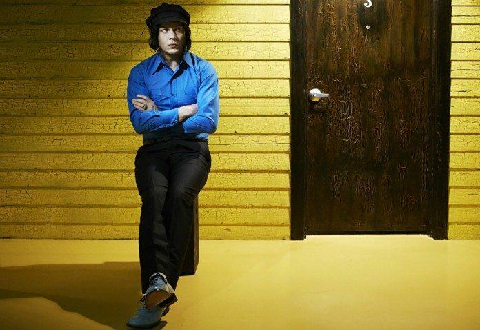 Jack White con camisa azul sobre un taburete delante de un muro amarillo.