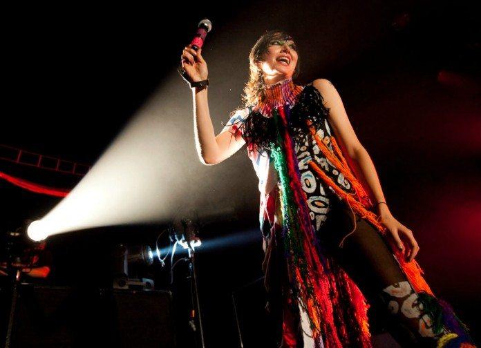 Karen O en directo iluminada por un foco.