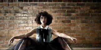 Kimbra con falda sentada junto a un muro de ladrillos.