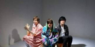 Klaxons sentados en un estudio fotográfico con ropa de colores.