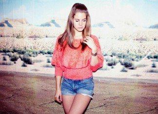 Lana Del Rey con un jersey rojo y unos shorts vaqueros posa en un decorado.