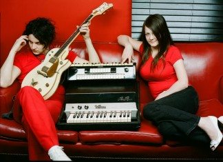 The White Stripes sobre un sofá con una guitarra y un acordeón.