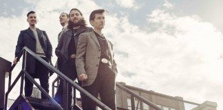 Arctic Monkeys en una escalera con el sol de fondo