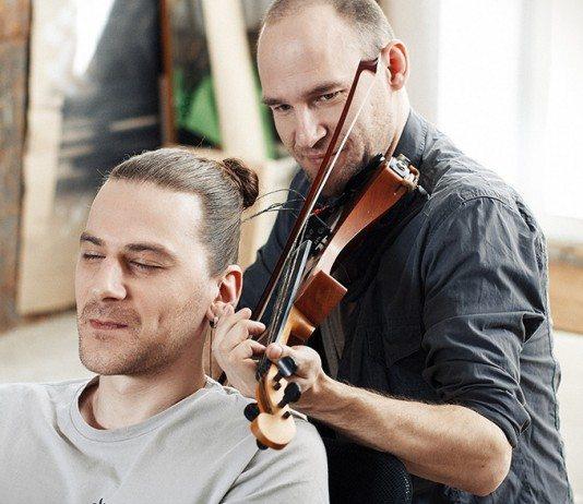 Eimantas Belickas tocando el violín con la melena de Tadas Maksimovas