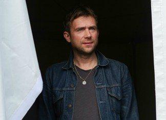 Damon Albarn con una cazadora vaquera entre cortinas blancas