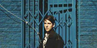 Owen Pallett en una pared y una puerta azul