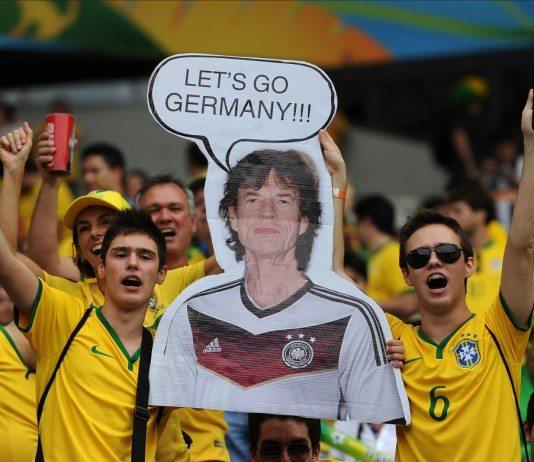 Aficionados de Brasil con un cartel de Mick Jagger con la camiseta de Alemania