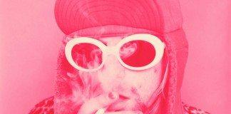 Kurt Cobain con gafas de sol blancas, un gorro y fumando, con un filtro rosa