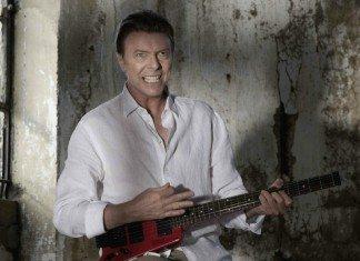 David Bowie tocando una guitarra sin clavijero en una casa en ruinas