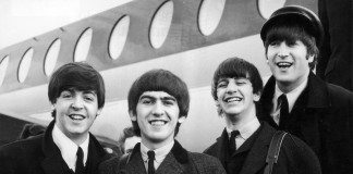 The Beatles frente a un avión, en blanco y negro