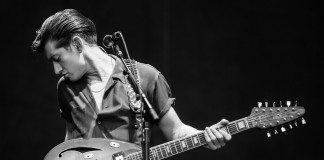 Alex Turner tocando la guitarra en directo.