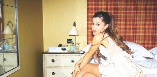 Ariana Grande sentada en la cama de una habitación.