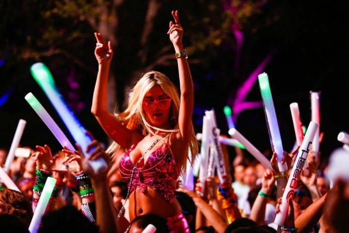 Chica baila subida a hombros en un festival.