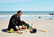 Hombre de negocios jugando en la playa.
