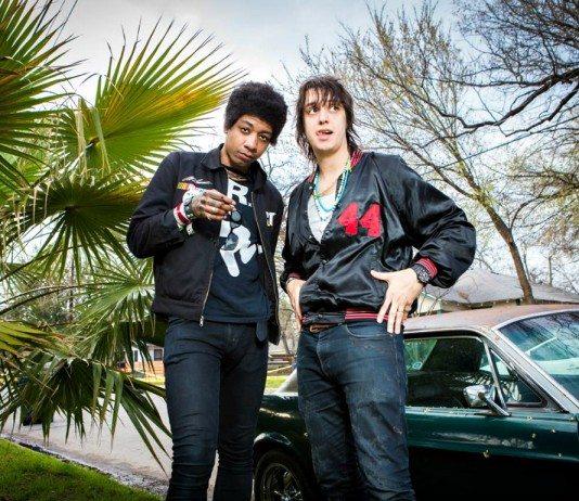 Honor Titus con Julian Casablancas en un jardín junto a un coche.