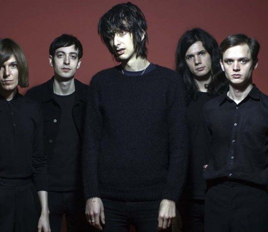 The Horrors con un fondo burdeos