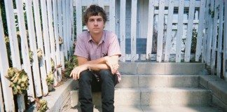 Kevin Morby sentado en las escaleras de un jardín.
