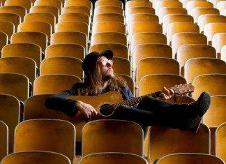 King Tuff sentado en un auditorio con una guitarra acústica