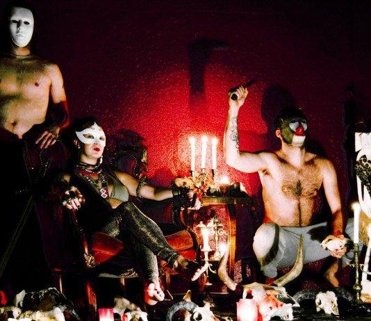 Miembros de GOAT con máscaras en una pared roja.