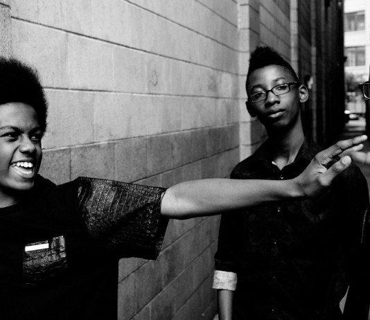 Miembros de Unlocking The Truth en un callejón en una foto en blanco y negro.