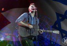 Chris Martin toca la guitarra en directo entre las banderas de Palestina e Israel.
