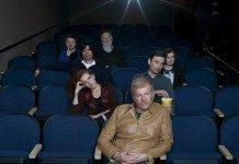The New Pornographers sentados en las butacas de un cine.